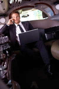 Handsome young businessman sitting in limousine, talking on mobi